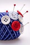 Broches dans la bille de laines avec des boutons Photos libres de droits
