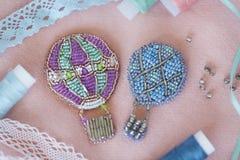 Broches perlées sous forme de montgolfiers ou ballons avec les perles et le surrounde d'argent, bleu-clair, gris, verts et violet Image stock