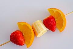 Brochette de fruit avec la fraise, papaye, orange à l'arrière-plan blanc Photographie stock libre de droits