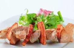 Brochette de porc avec des verts de salade images libres de droits