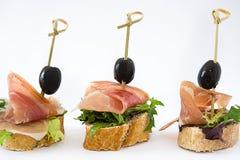 Brochettes espagnoles de jambon de serrano avec les olives et la laitue sur le fond blanc Images stock