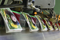 Brochure and magazine stitching process. Close-up of the  offset conveying process of a full-automatic stitching unit. Print shop Stock Images