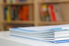 Brochures on Table. A stack of multiples type of brochures on a white table with a book case at the background Royalty Free Stock Image
