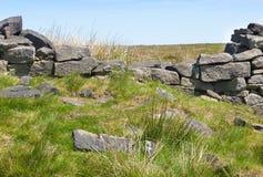 Brocken dry stone wall on moorland. Brocken dry stone wall of gritstone on moorland Royalty Free Stock Image