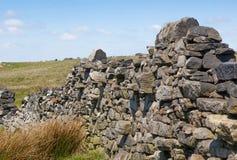 Brocken dry stone wall on moorland. Brocken dry stone wall of gritstone on moorland Royalty Free Stock Images