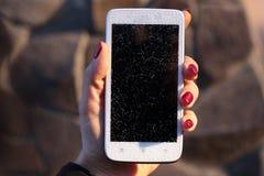 Brocken-Glas am weißen Handy in der weiblichen Hand lizenzfreies stockbild