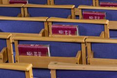Holy Bibles and Chairs in Church. Brockenhurst, England - October 23, 2018: Red holy bibles on a blue chairs in the church of Brockenhurst royalty free stock images