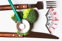Brocoli avec le stéthoscope sur l'échelle de poids dieting Photographie stock libre de droits