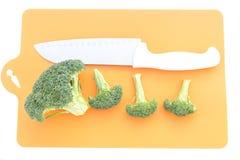 Brocoli et couteau sur les planches à découper de plastique Image stock