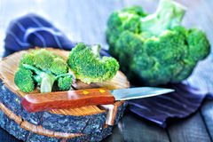 Brocoli. Raw brocoli and knife on the wooden background royalty free stock images