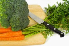 Brocolli and carots. A bundle of both carrots and Brocolli on a cutting board with a knife Royalty Free Stock Image