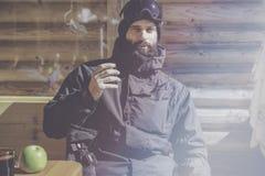 Brodaci potomstwa snowboarded brać odpoczynek po przejażdżki sesi Młody człowiek pije filiżankę gorąca herbata na pogodnym tarasi obraz stock