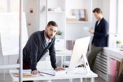 Brodata biznesmen pozycja przy biurkiem obrazy royalty free