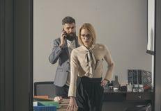 Brodata mężczyzna rozmowa na smartphone w biurze Zmysłowy formalny i odziewamy Biznesmen i bizneswoman zdjęcie stock