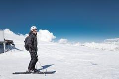 Brodata m?ska narciarka w he?mie i masce narciarskiej stoi na nartach przeciw t?u nakrywa? g?ry i obraz royalty free