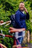 Brodata samiec w parku opowiada mądrze telefonem obrazy stock