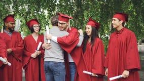 Brodatego mężczyzna dumny nauczyciel gratuluje absolwentów trząść ręki i ściska one outdoors w szkoła wyższa kampusie podczas gdy zbiory wideo