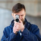Brodatego mężczyzna fachowy kamerzysta obserwuje 8mm mo i strzela Obraz Stock