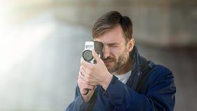 Brodatego mężczyzna fachowy kamerzysta obserwuje 8mm mo i strzela Zdjęcia Royalty Free