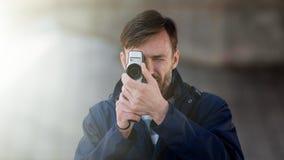 Brodatego mężczyzna fachowy kamerzysta obserwuje 8mm mo i strzela Zdjęcie Stock