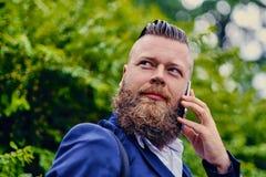 Brodatego modnisia męski używa smartphone plenerowy zdjęcia royalty free