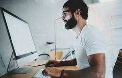 Brodatego modnisia oka szkieł fachowy jest ubranym działanie przy nowożytnym loft biurem z komputerem stacjonarnym pusty biel fotografia royalty free