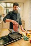 Brodatego szefa kuchni kulinarny mięso w niecce na kuchni fotografia stock