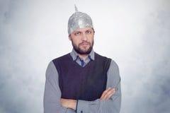 Brodaty śmieszny mężczyzna w nakrętce aluminiowa folia Pojęcie sztuki fobie zdjęcie stock