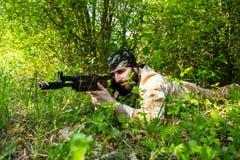 Brodaty żołnierz z karabinem w drewnach Zdjęcie Stock