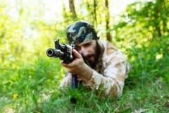 Brodaty żołnierz z karabinem w drewnach Obraz Stock