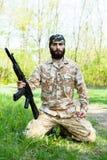 Brodaty żołnierz z karabinem w drewnach Zdjęcia Royalty Free