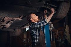 Brodaty auto mechanik w mundur naprawie samochodowy ` s zawieszenie z wyrwaniem podczas gdy stojący pod podnośnym samochodem w na obrazy royalty free