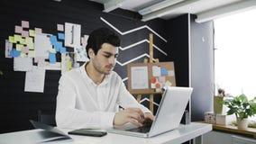 Brodaty biznesmen pisać na maszynie na jego laptop klawiaturze w loft biurze zdjęcie wideo