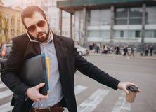 Brodaty biznesmen z filiżanką łapie taxi No ma czasu, on iść opowiadać na telefonie aktywnym Obraz Stock