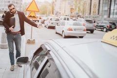 Brodaty biznesmen z filiżanką łapie taxi No ma czasu, on iść opowiadać na telefonie aktywnym Zdjęcia Stock