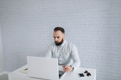 Brodaty biznesmena obsiadanie przy biurkiem w biurze Obraz Stock