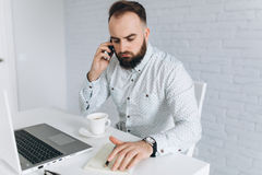 Brodaty biznesmena obsiadanie przy biurkiem w biurze Obrazy Stock