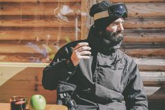 Brodaty chłodno snowboarded bierze odpoczynek po przejażdżki sesi Młody człowiek pije filiżankę gorąca herbata na pogodnym tarasi zdjęcia royalty free