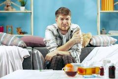Brodaty chory mężczyzna z płomienicy obsiadaniem na kanapie w domu Choroba, grypa, bólowy pojęcie domowy relaks Opieka zdrowotna fotografia royalty free