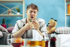 Brodaty chory mężczyzna z płomienicy obsiadaniem na kanapie w domu Choroba, grypa, bólowy pojęcie domowy relaks Opieka zdrowotna zdjęcie stock