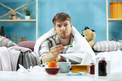Brodaty chory mężczyzna z płomienicy obsiadaniem na kanapie w domu Choroba, grypa, bólowy pojęcie domowy relaks Opieka zdrowotna fotografia stock