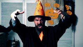 Brodaty czarownik macha jego ręki i czyta czary na Halloweenowym pojęciu uczty Halloween świętowania i przyjęcia zbiory
