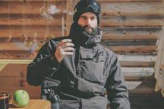 Brodaty dorosły snowboarded brać odpoczynek po przejażdżki sesi Młody człowiek pije filiżankę gorąca herbata na pogodnym tarasie  obraz royalty free