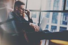 Brodaty elegancki biznesmen pracuje przy nowożytnym loft biurem Mężczyzna obsiadanie w rocznika krześle, mienie w ręki szkle Zdjęcia Stock