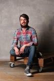 Brodaty facet siedzi z krzyżować nogami w kolorowej koszula i cajgach Obrazy Stock