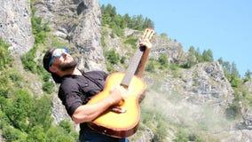 Brodaty facet w czarnej koszula i okularach przeciwsłonecznych udaje bawić się dymiącą gitarę akustyczną Dziwaczny śmieszny wideo zbiory