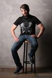 Brodaty facet w koszulce z motylim obsiadaniem na prętowej stolec greaser Fotografia Stock
