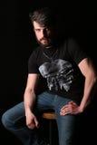 Brodaty facet w koszulki obsiadaniu na prętowej stolec zakończenie W górę czerń Zdjęcia Royalty Free