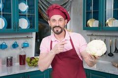 Brodaty facet wskazuje na kalafiorze w ręce Uśmiechnięty szef kuchni trzyma białego dużego kalafioru w ręce Fotografia Stock