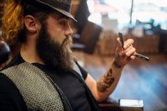 Brodaty fryzjer męski w kapeluszu z prostą żyletką w ręce Fotografia Royalty Free
